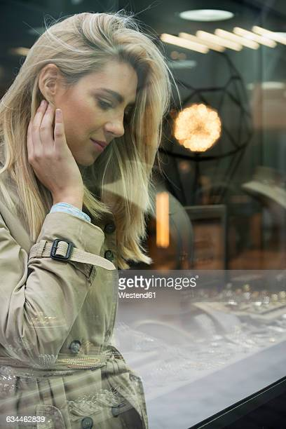 Young woman looking through window display