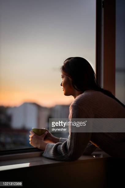 young woman looking through window during coffee time. - sunrise contemplation stock pictures, royalty-free photos & images