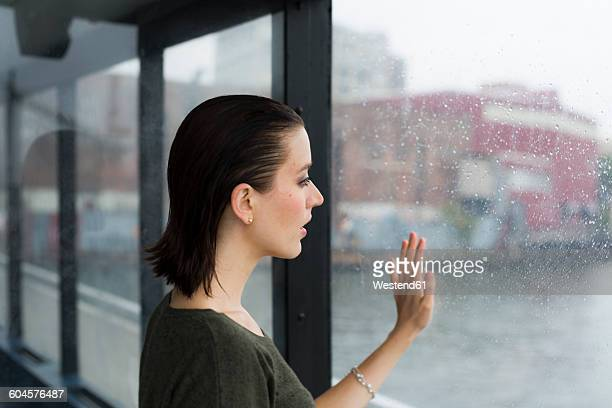 Young woman looking through window of an excursion boat on a rainy day