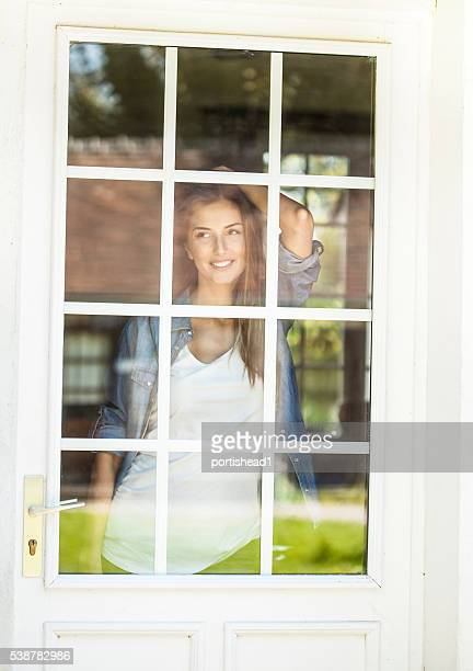 Young woman looking through window of french door