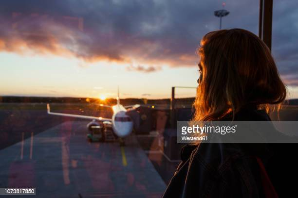 young woman looking through window on plane at the airport at sunset - volare foto e immagini stock