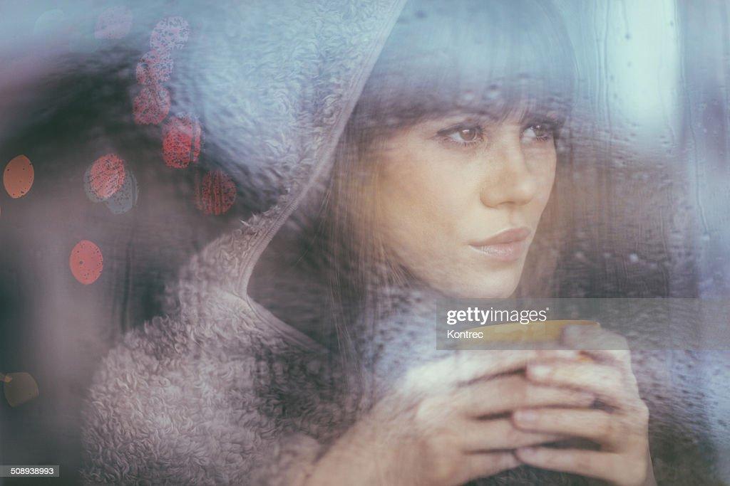 Jeune femme regardant à travers une fenêtre sur un jour de pluie : Photo