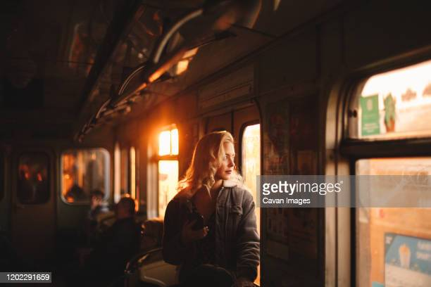young woman looking through window traveling in subway train - morgen stock-fotos und bilder