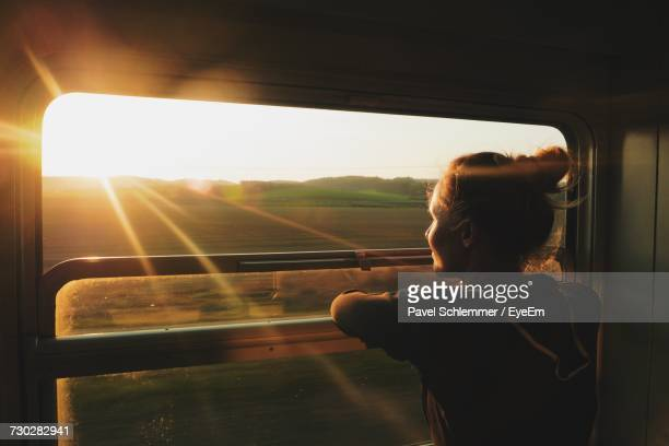 Young Woman Looking Through Window While Traveling In Train During Sunset