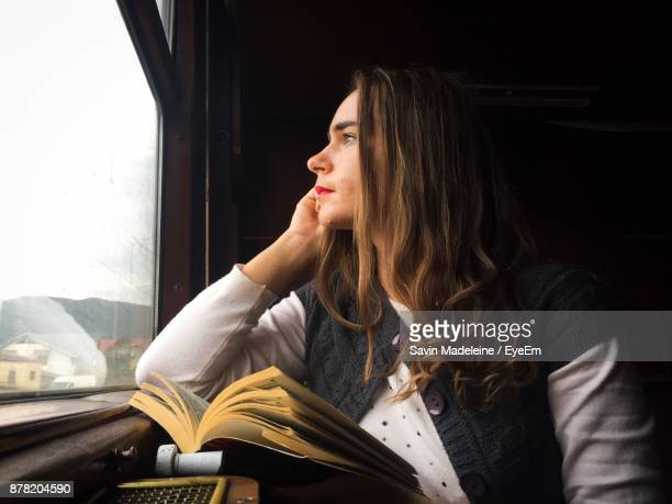 young woman looking through window while traveling in train - lady madeleine stock-fotos und bilder