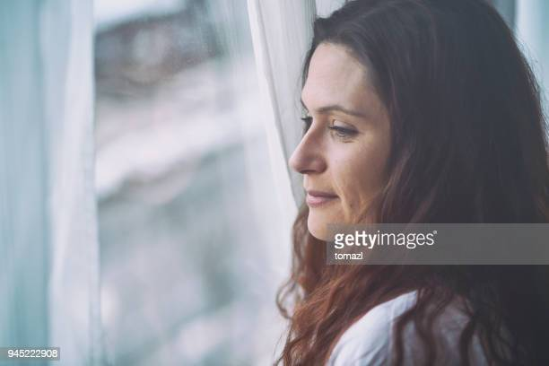 young woman looking through window with reflection - introspection stock pictures, royalty-free photos & images
