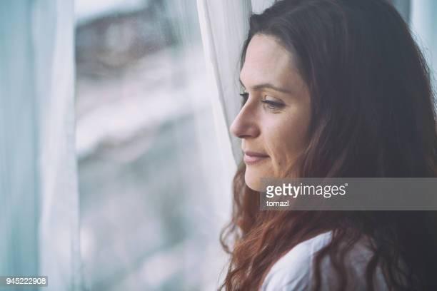 junge frau, die durch fenster mit reflexion - introspektion stock-fotos und bilder