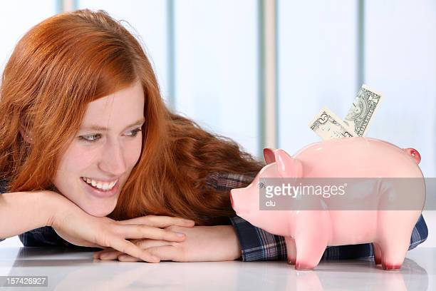 Young woman looking to a piggy bank