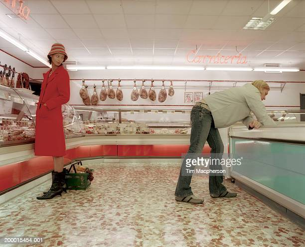 young woman looking towards man in meat section of supermarket - flirting stock pictures, royalty-free photos & images