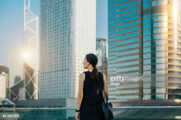 young woman looking towards the busy and energetic city skyline of hong kong - back to work stock pictures, royalty-free photos & images