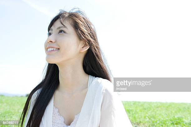 Young woman looking up and smiling on grass