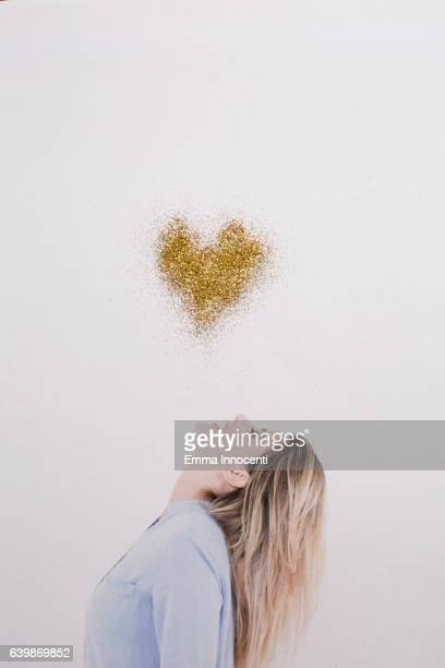 Young woman looking up at a golden heart