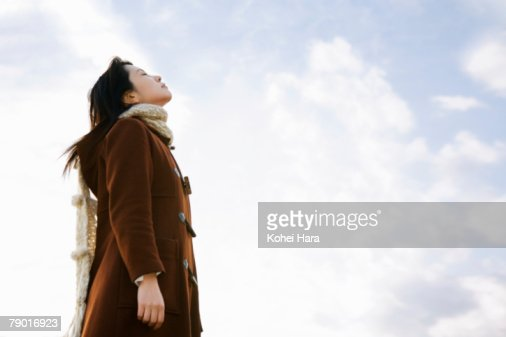 young woman looking up at sky stock photo