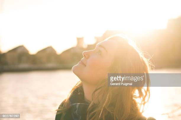 young woman looking up at the sky on a sunny afternoon - sunlight stock-fotos und bilder