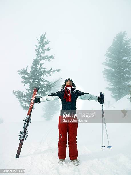 young woman looking up holding skies and ski poles, full length - ski wear stock pictures, royalty-free photos & images