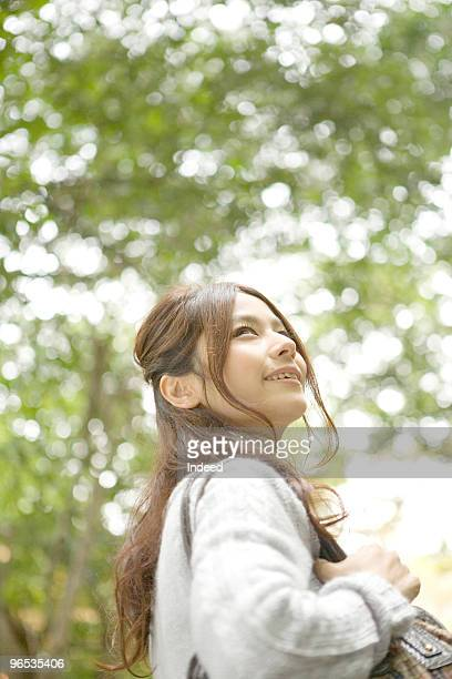 Young woman looking up in forest, smiling