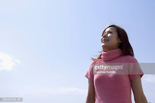Young woman looking up, outdoors, low angle view