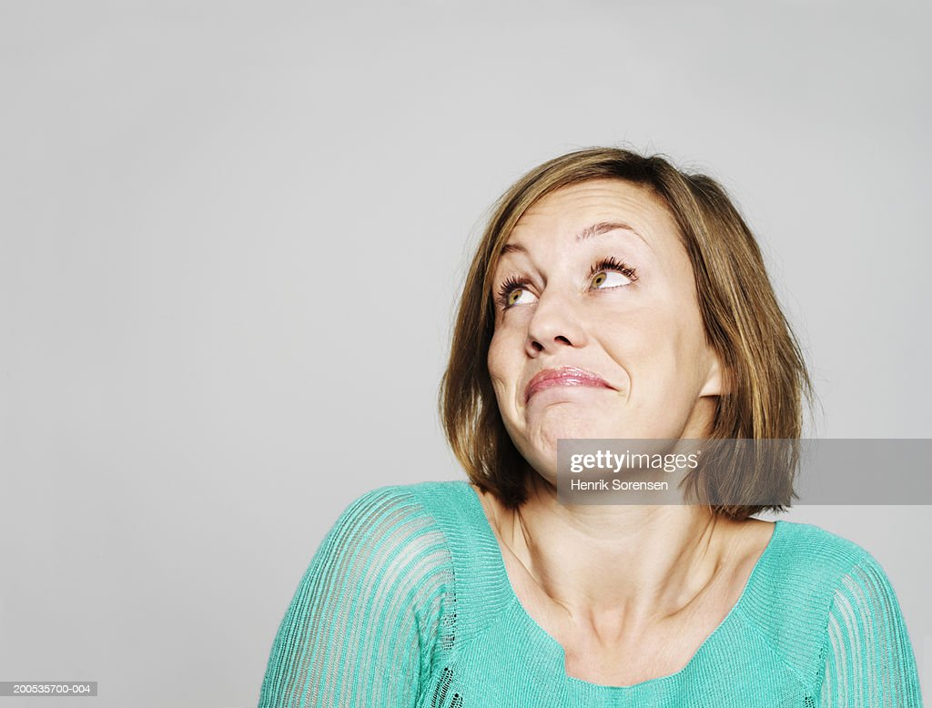 Young woman looking up, shrugging shoulders : Stock Photo
