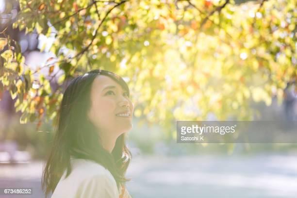 Mujer joven mirando debajo de las hojas verdes
