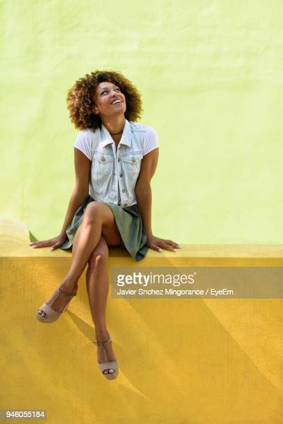 young woman looking up while sitting against yellow wall - retaining wall stock pictures, royalty-free photos & images