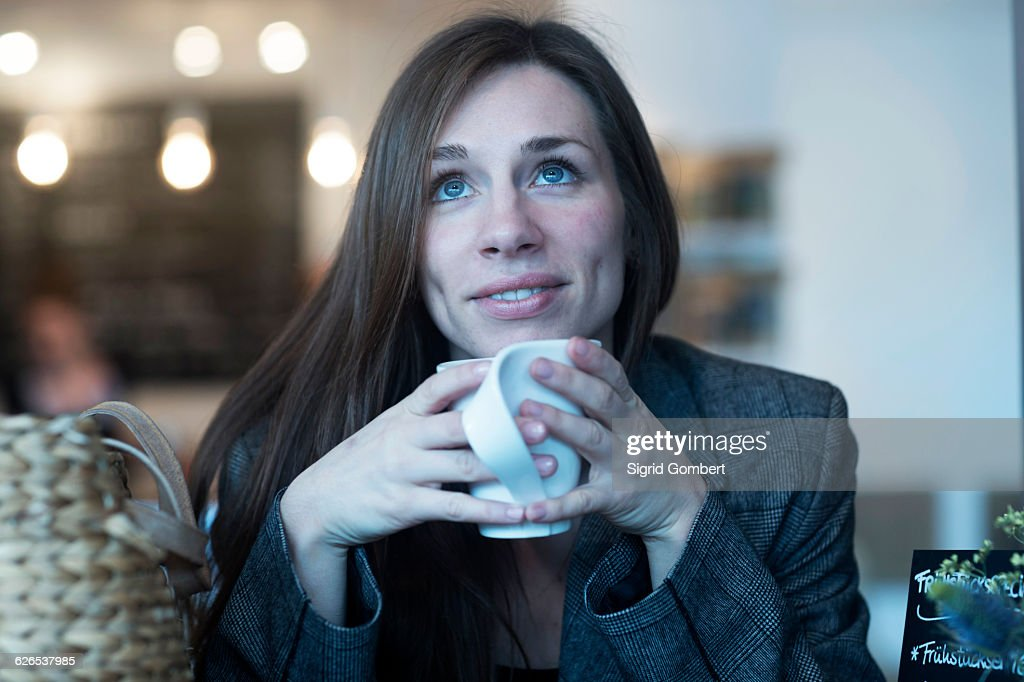 Young woman looking up whilst drinking coffee in cafe : Stock-Foto