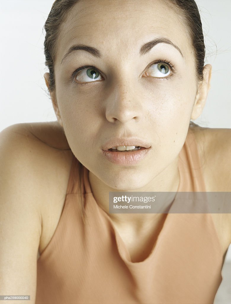 Young woman looking up with raised eyebrows, close-up : Stockfoto