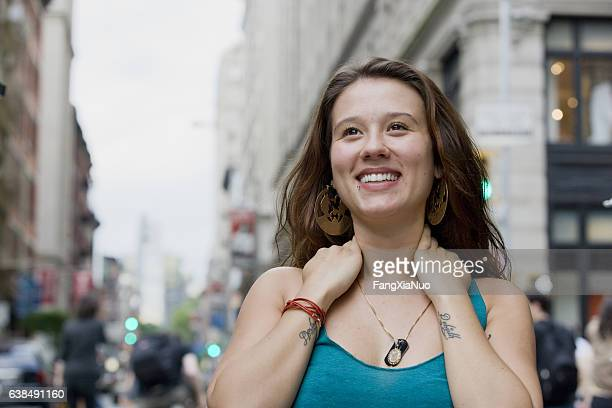 young woman looking upward in downtown city - new yorker building stock photos and pictures