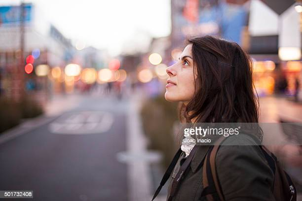 Young woman looking upwards at Cuba Street, Wellington, New Zealand