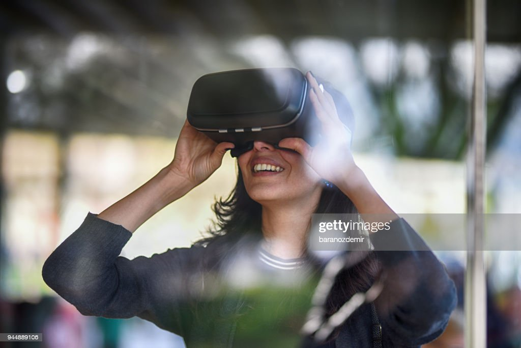 Young woman looking with VR behind the glass : Stock Photo