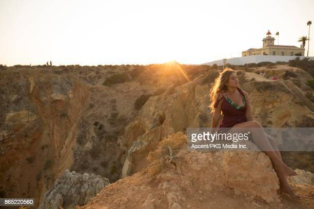 young woman looks across coastal landscape from raised viewpoint - mb media stock pictures, royalty-free photos & images