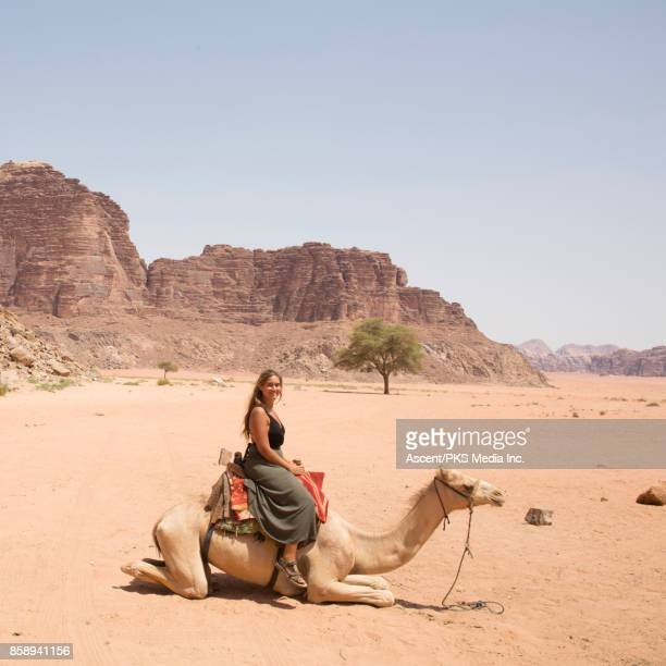 Young woman looks across desert landscape from camel