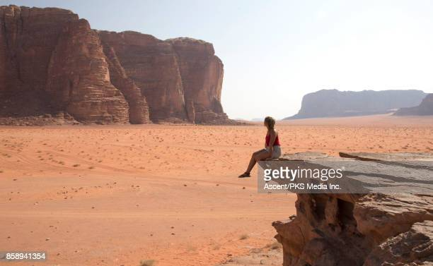 Young woman looks across desert landscape from raised viewpoint