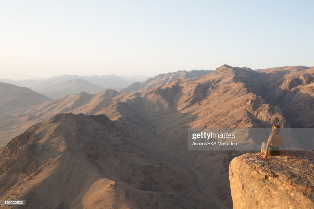 Young woman looks across desert landscape from raised viewpoint : Stock Photo