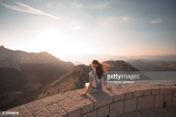 Young woman looks across mountains and valley, sunrise