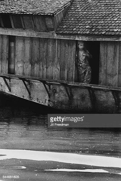 A young woman looks across the water from a houseboat in Srinagar India 1978