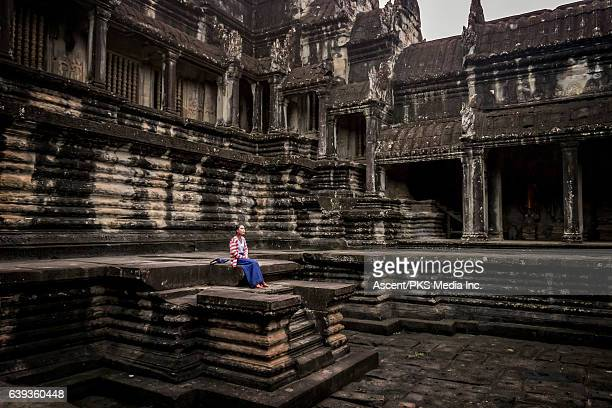 Young woman looks across to ruins, Angkor Wat