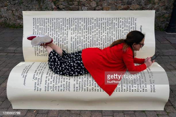 Young woman looks at her smartphone in Cartes, Cantabria, Spain, on June 6 which has installed a book-shaped bench in the middle of the Camino Real,...