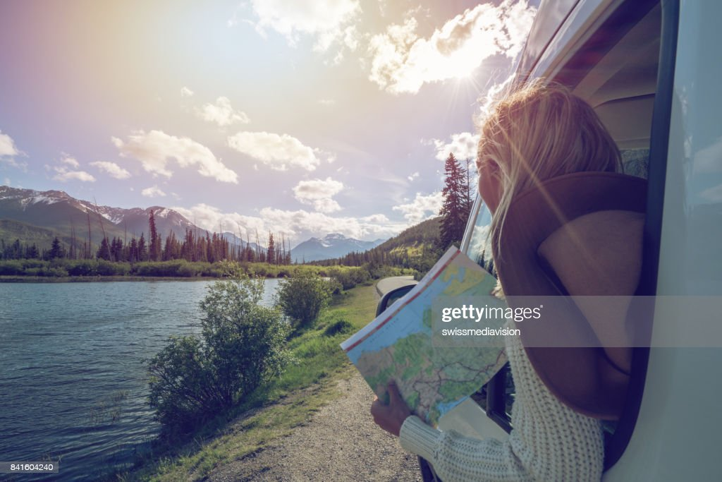 Young woman looks at road map near mountain lake : Stock Photo