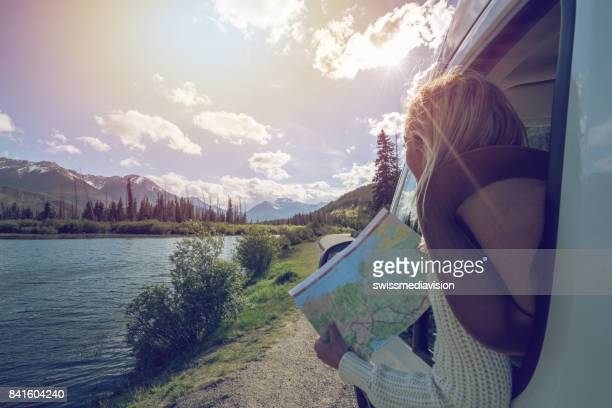 Young woman looks at road map near mountain lake