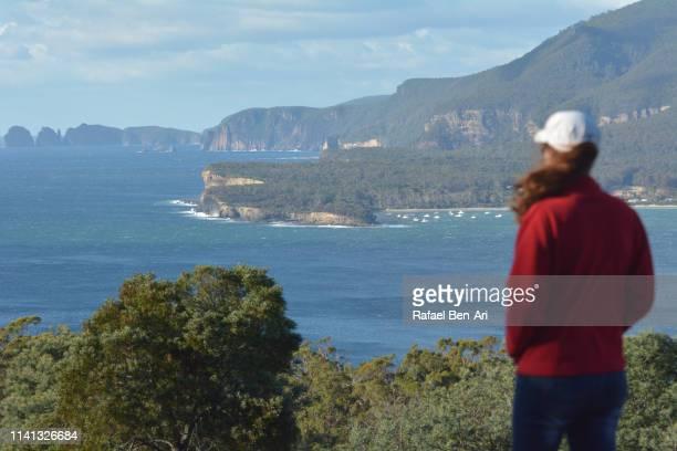 young woman looks at sea cliffs in tasmania australia - rafael ben ari stock-fotos und bilder