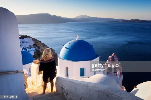 young woman looks at the marine landscape, santorini, oia, greece - oia santorini foto e immagini stock