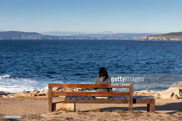 Young woman looks at the sea horizon of the Coruña estuary in the public park of the Torre Hercules lighthouse on July 16 A Coruña, Galicia,Spain.