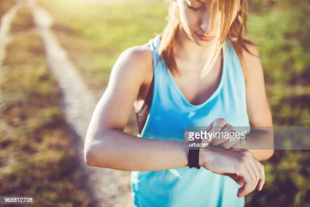 una mujer mira el reloj después de correr. - pulsera fotografías e imágenes de stock