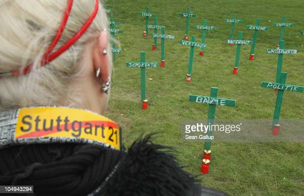 A young woman looks at wooden crosses pounded into the ground by activists one for each of the 25 trees recently removed from Schlossgarten park next...