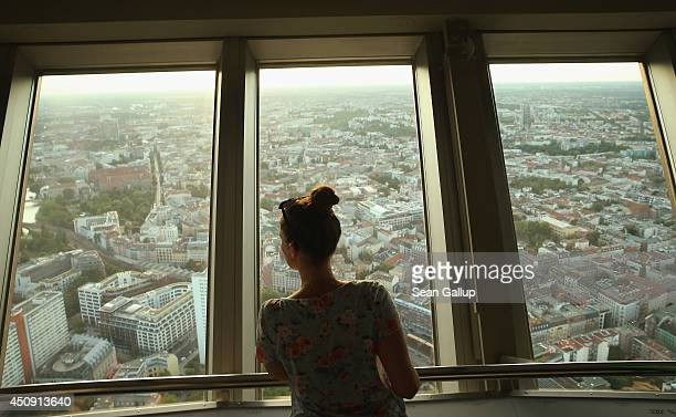 A young woman looks down at central Berlin from the broadcast tower at Alexanderplatz on June 18 2014 in Berlin Germany Alexanderplatz a crossing...