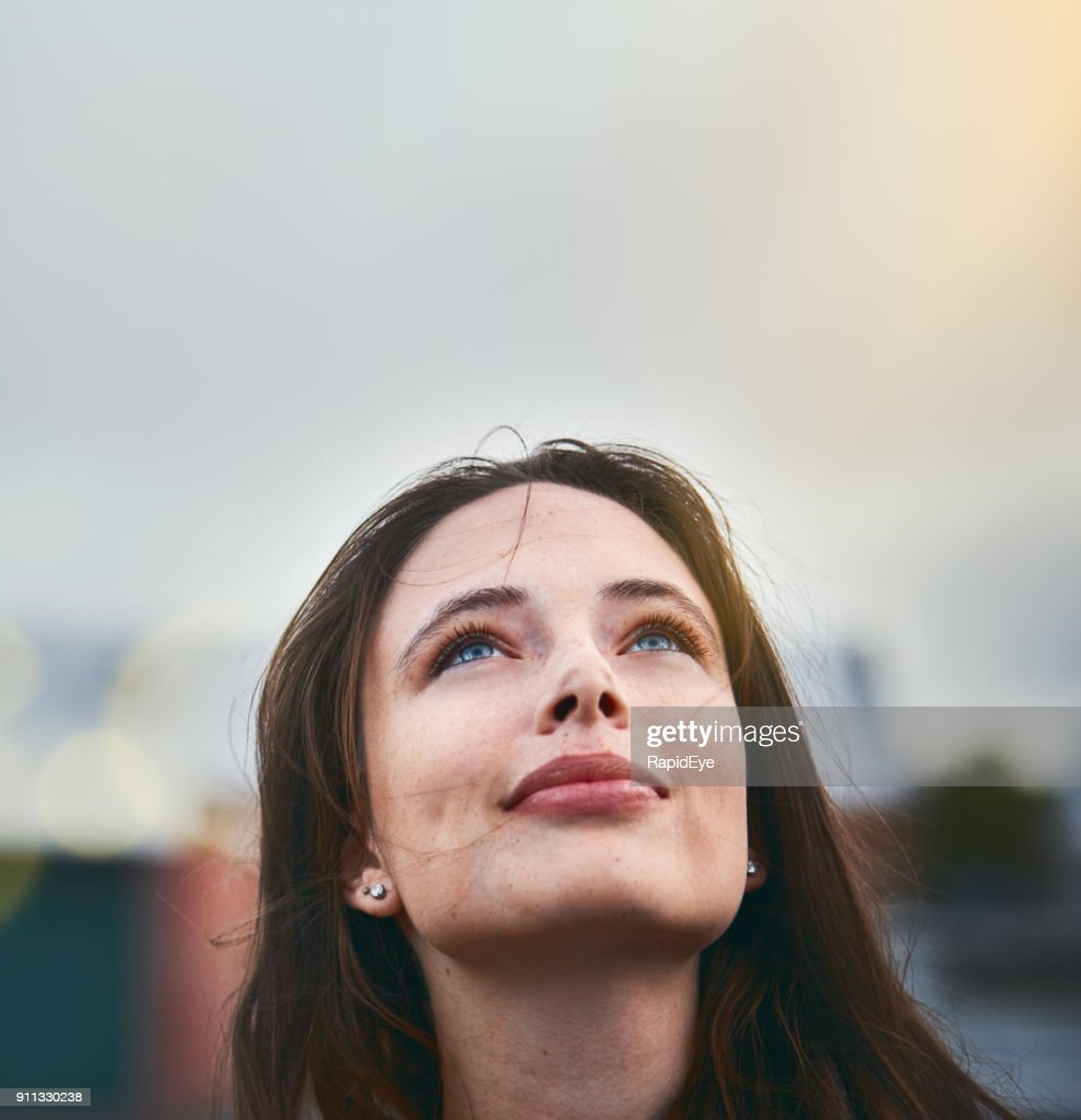 Young woman looks hopeful as she raises her eyes towards the sky : Stock Photo