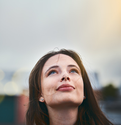 Young woman looks hopeful as she raises her eyes towards the sky - gettyimageskorea