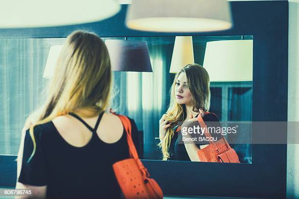 Young woman looks in the mirror before going out