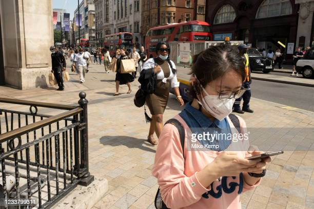 Young woman looks intently at his smartphone as the national coronavirus lockdown three eases towards the planned 'Freedom Day' in just over two...