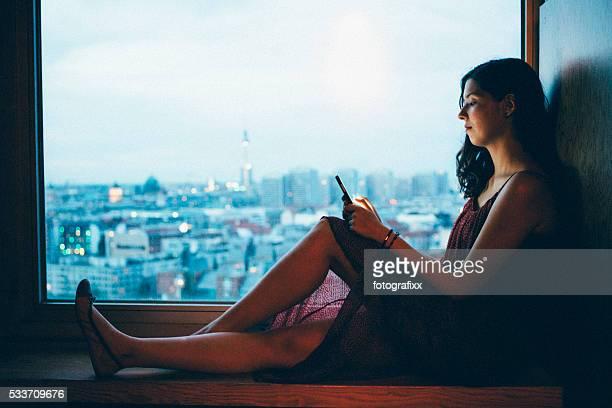 Junge Frau sieht in Smartphone, beleuchtete skyline der Stadt Hintergrund
